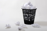 black wasterbasket with wastepaper