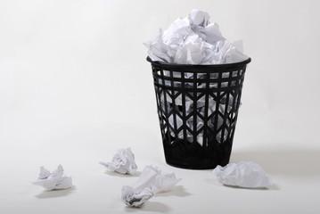 black wasterbasket with wastepaper