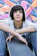 garçon devant un mur de graffitis avec une planche à roulettes