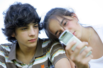 jeune fille avec téléphone portable près d'un garçon