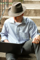 Young Man Wearing Hat on Stairs With Laptop 3