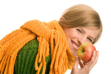 Pretty autumnal teenage girl holding apple laughing