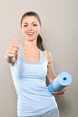 Sportliche junge Frau mit Yogamatte macht Top-Daumen
