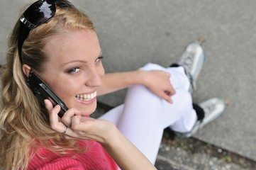 Woman wearing rollerblades calling with mobilephone