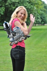 Young woman with rollerskates giving good bye