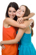 Two young woman embrace and smile