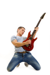 picture of a guitarist playing his guitar on knees