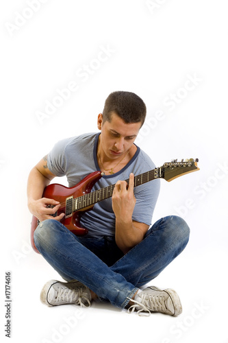 seated guitarist playing an electric guitar