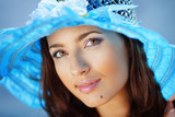 Beautiful face of woman in blue summer hat
