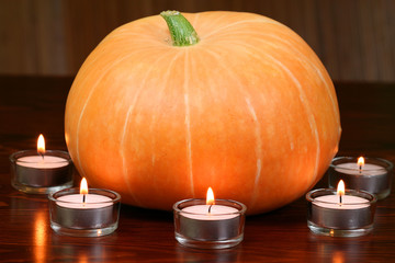 Pumpkin in light of candles