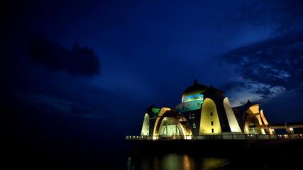 Sun sets over The Selat Melaka Mosque, Malacca, Malaysia.