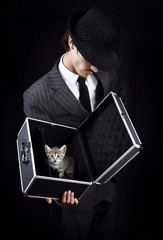 Businessman in grey suit holding open metal box with kitten in i