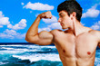 Muscular man showing his biceps on the beach