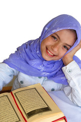 Little girl reads Qoran and smiles