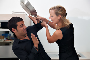 a woman beating a man with a pan