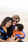 Multiracial family sitting on beach poster