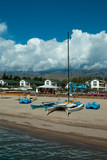 Catamarans at the seashore in front of the houses and mountains