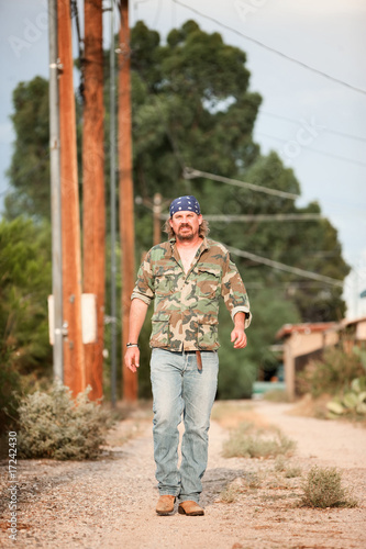 Man in camoflauge walking on dirt road