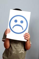 bambino con cartello faccia triste