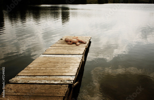 Forgotten doll on a wooden mooring