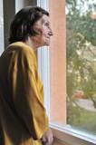 Solitude - senior woman looking through window poster