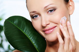 Woman applying  moisturizer cream with a  fresh leaf at face
