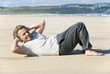 Happy mature man exercising on beach.