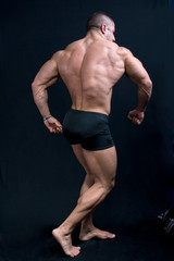 a muscular man posing artistic, back double biceps