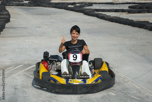 prety brunette driving a kart on karting circuit
