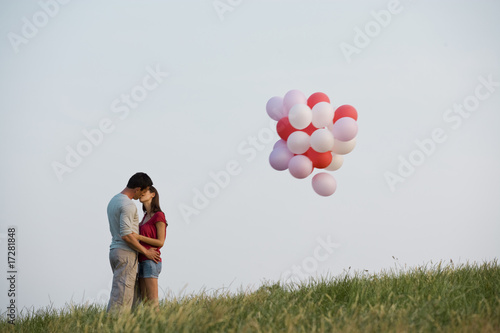 A young couple kissing, a bunch of balloons floating away