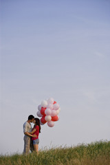 A young couple kissing, holding a bunch of red balloons