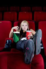 Young woman alone in cinema with popcorn .