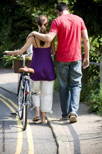 A man and woman walking together with a bicycle and shopping