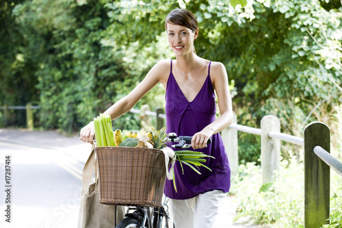 A young woman pushing a bicycle with a basket full of shopping