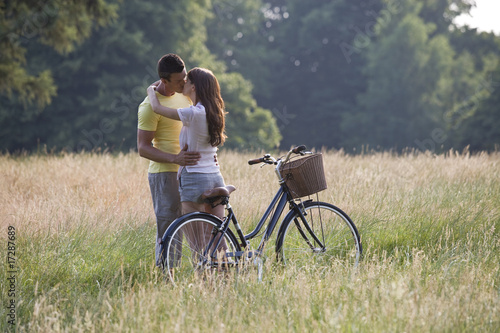 A young couple standing in a field kissing
