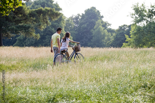 A young couple pushing a bicycle through a field