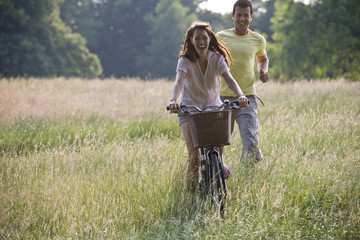 Woman riding bicycle through field, boyfriend running after her
