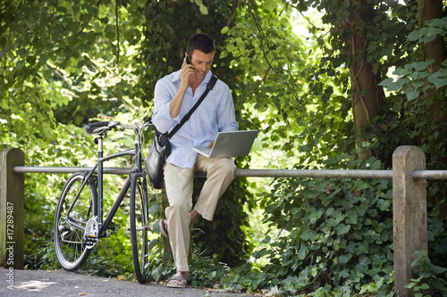A man sitting on railings using a laptop and mobile phone