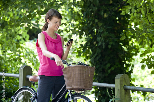 A young woman on a bicycle using a mobile phone