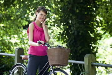 A young woman on a bicycle speaking on a mobile phone