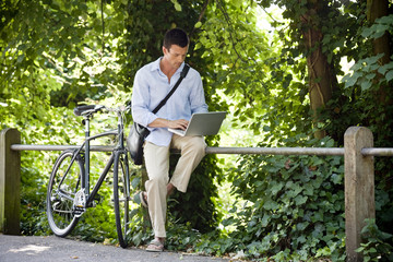 A man sitting on railings using a laptop