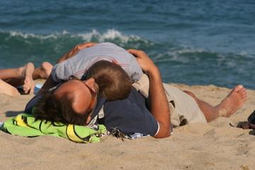 Niño durmiendo sobre su padre en la playa 2