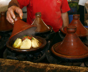 Market cook holding a cover of a tajine dish (traditional casser
