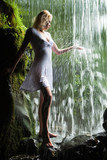 Blond girl in white dress enjoying a waterfall