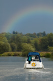 riverboat approaching a rainbow in an overcast sky poster