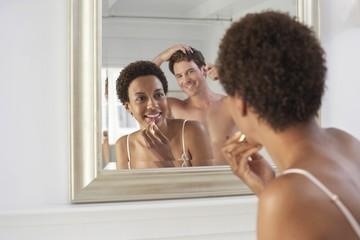 Couple Using Bathroom Mirror