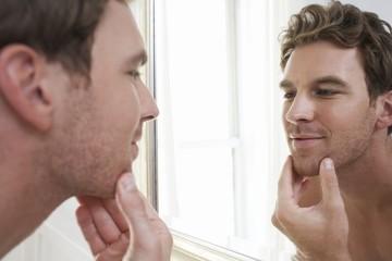 unshaven man looking in bathroom mirror