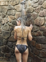young woman having shower by stone wall  back view  outdoors
