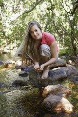 Portrait of teenage girl 16-17 years squatting on stone by stream in forest, smiling