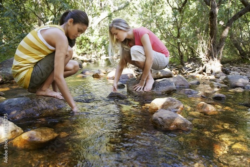 Two teenage girls 16-17 years squatting on stone by stream in forest, hands in water